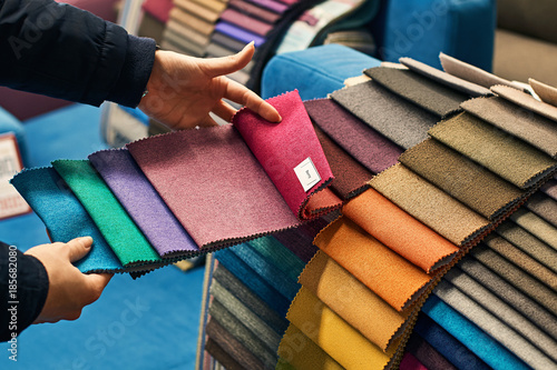 Fotobehang Stof Young woman is making her decision while choosing a color of a fabric from a huge variety in a shop