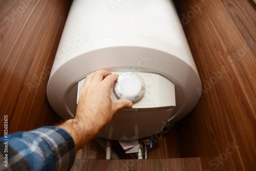 Man hand regulate heat in Condensing Boiler, Combi Boiler for house energy saving. Gas Boiler, Boiler Supplies Concept.