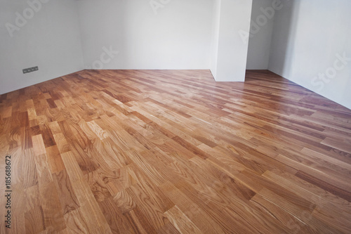 Obraz Flooring from a parquet oak board in an interior with bright light from a window. - fototapety do salonu