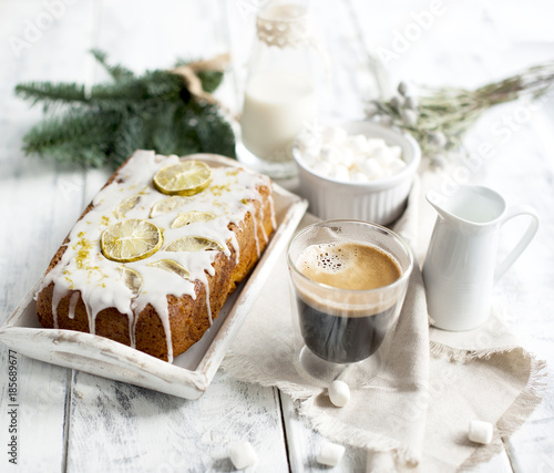 Poster a glass with coffee and small marshmallow, a cupcake and a branch of a Christmas tree, on a white wooden background