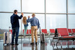 Full length back view of joyful adult father and grandfather are having fun with little girl. They are standing near big window at airport with suitcases before boarding. Copy space in the right side