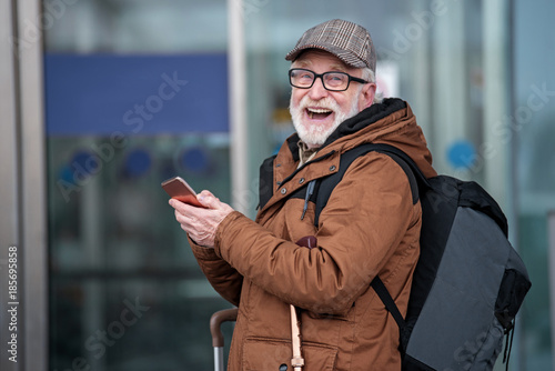 e4b22499d35 Laughing old gray-haired man with beard is standing outdoors with backpack  and mobile phone. He is looking at camera with wide smile