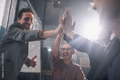 Obraz na plátně  Low angle outgoing lady and beaming men putting arms together while sitting at table in office