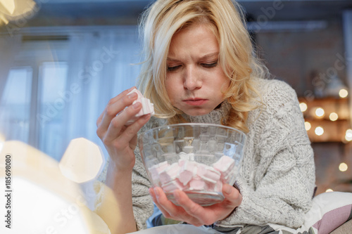 Low angle portrait of eating woman sitting at home Canvas-taulu