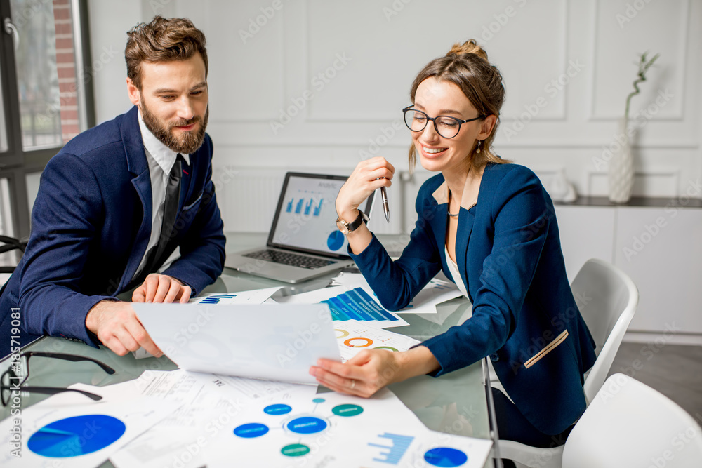 Fototapeta Marketer or analityc manager team dressed in suits working with paper charts and laptops at the white office interior