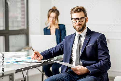 Obraz Portrait of a businessman dressed in suit working on documents with female assistant on the background at the white office interior - fototapety do salonu