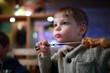 Kid eating kebab on skewer