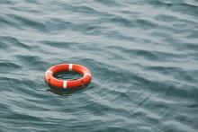 Orange Lifebuoy On The Waves A...