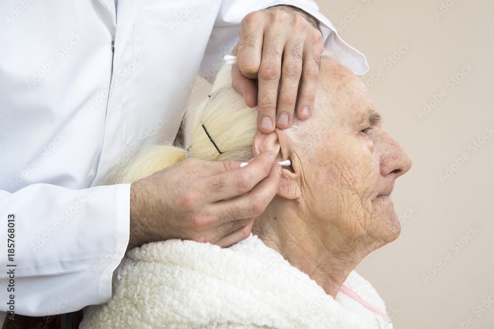 Fototapeta Czyszczenie uszu starej kobiecie patyczkiem. Higiena i opieka nad osobą starą.