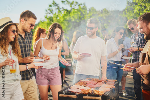 Foto Group of people standing around grill, chatting, drinking and eating