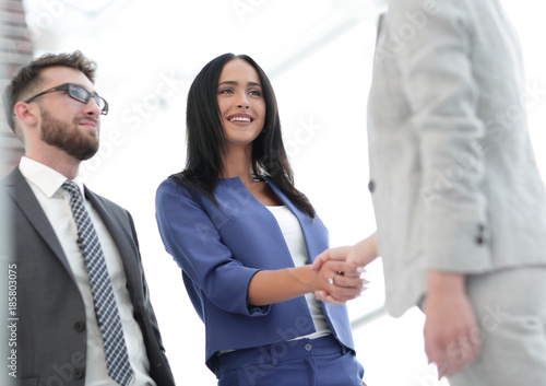 Businesswomen Shaking Hands In Modern Office Canvas Print