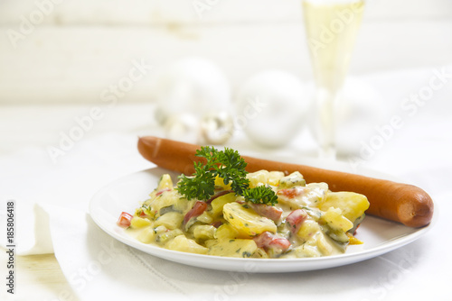 potato salad with wiener sausage and parsley garnish on a white wooden table, typical german