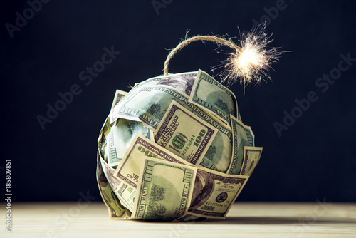Photo  Bomb of money hundred dollar bills with a burning wick