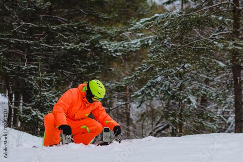 Poster Wintersporten Snowboarder checks his equipment