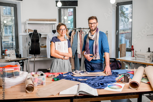 Portrait Of A Couple Of Fashion Designers Working With Fabric And Clothing Sketches At The Studio Full Of Tailoring Tools And Equipment Buy This Stock Photo And Explore Similar Images At