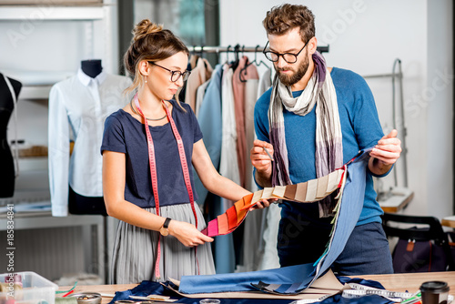 Couple Of Fashion Designers Choosing Fabric Standing At The Studio Full Of Tailoring Tools And Equipment Buy This Stock Photo And Explore Similar Images At Adobe Stock Adobe Stock