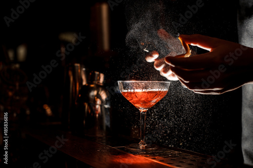 Bartender sprays an orange peel in cocktail glass