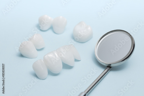 Foto  Dental mirror and dentures on a light blue background