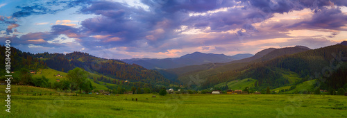 Fototapeta Carpathian mountains summer landscape with cloudy colorful sky and village at sunset, natural travel background obraz na płótnie