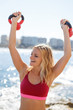 Happy young blonde woman pushing up kettlebells, outdoor workout