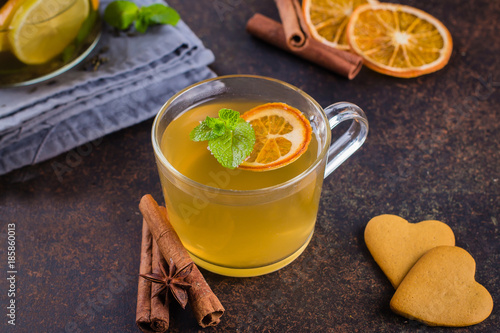 Stickers pour portes The Hot Citrus Tea with orange, lemon, cinnamon, mint, anise star and carnation on dark table nbackground. Winter Healthy Cold Drink with cookies shape heart.