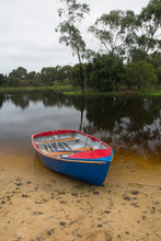 A Red Blue Canoe Rests On A Sandy Shore With Forest As A Background.
