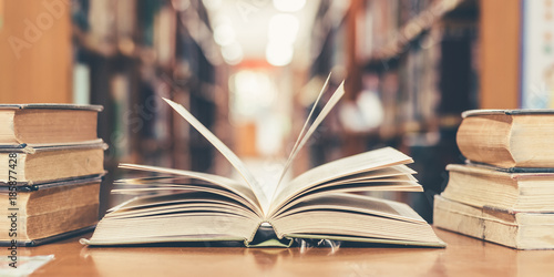 Obraz Book in library with old open textbook, stack piles of literature text archive on reading desk, and aisle of bookshelves in school study class room background for academic education learning concept - fototapety do salonu