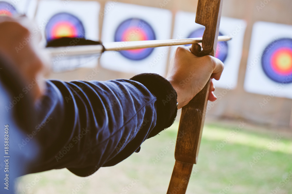 Fototapeta Archer holds his bow aiming at a target
