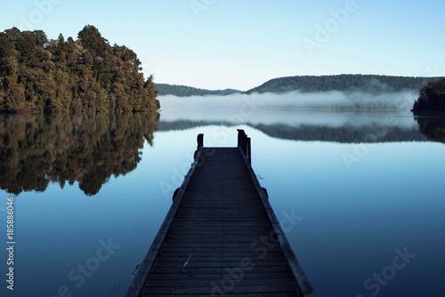 Lago en calma con pequeño embarcadero y reflejo de niebla y árboles Canvas Print