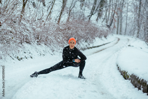 Poster Glisse hiver Woman wearing black and orange sportswear training exercising stretching legs outside during winter snowy day. Healthy lifestyle and cold weather concept.