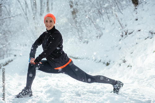 Poster Glisse hiver Woman runner in black and orange sportswear stretching legs before run. Beautiful american athlete girl working out in snowy winter park. Fitness and motivation concept.