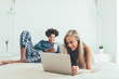 Young beautiful interracial couple relaxed lying down in bed on the computer and mobile phone