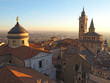 Bergamo, Italy. The old city. Aerial view of the Basilica of Santa Maria Maggiore and the chapel Colleoni during the sunset. In the background the Po plain