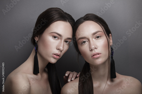 Photo  Fashion portrait of two beautiful slim sexy young girls twins sisters with clear