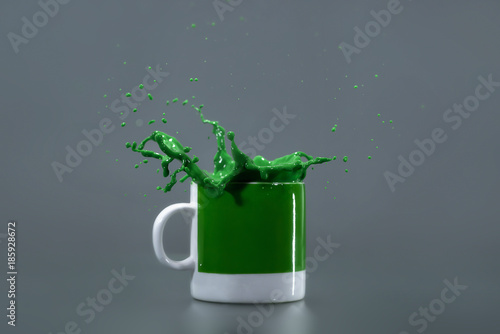 Green liquid splashing out of a green mug