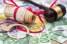 Handcuffs And Euro Bills And Wooden Gavel As Crime Concept