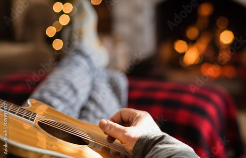Closeup of man's hand strumming guitar with feet up in front of a cozy fire Slika na platnu