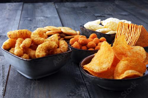 Fotografía  Salty snacks. Pretzels, chips, crackers in bowls