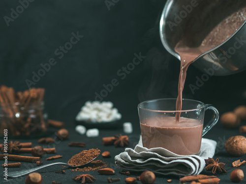 Poster Chocolate Pouring tasty hot chocolate cocoa drink into glass mug with ingredients on black table. Copy space Dark background. Low key.