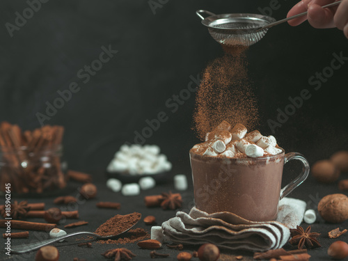 Tuinposter Chocolade Hand sprinkled cinnamon powder on glass mug with hot chocolate cocoa drink. Copy space. Dark background. Low key. Winter food and drink concept.