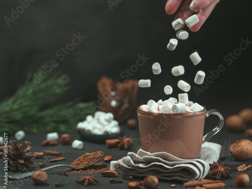 Tuinposter Chocolade Marshmallows falls from hand in glass mug with hot chocolate cocoa drink. Copy space. Winter food and drink concept. Flying marshmallow. Dark background. Low key.