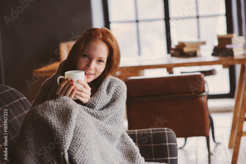 Obraz young sick woman healing with hot drink at home on cozy couch, wrapped in knitted blanket - fototapety do salonu