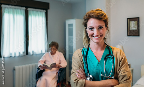 Pretty female doctor posing in a geriatric clinic with elderly lady in a wheelchair