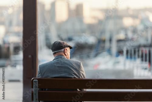 Fototapeta Hombre adulto irreconocible sentado en un banco frente al puerto