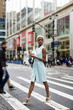 USA, New York, young blonde African American woman with cup of coffee and smart phone crossing street