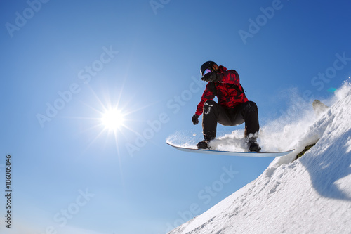 fototapeta na ścianę Snowboarder jumping from the springboard against the sky