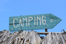 Blue Handmade Handwritten Painted Vintage Camping Sign Made Out Of Wood Showing In To The Right Side Direction On A Palapa Roof With Blue Sky Background