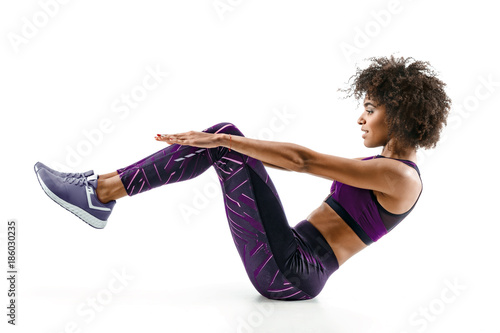 Fotografia  Beautiful young girl doing fitness exercise sit-ups, abs