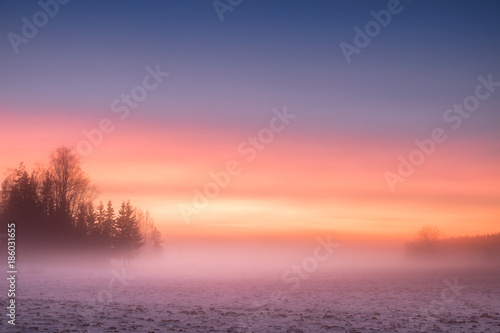 Spoed Foto op Canvas Zalm Foggy and colorful sunset with peaceful landscape at winter evening in Finland