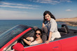 young women in red cabriolet at seaside